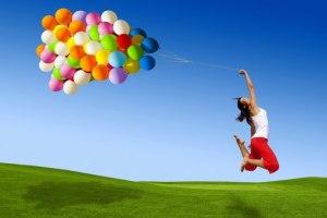 mujer-saltando-playera-blanca-pantalon-rojo-muchos-globos